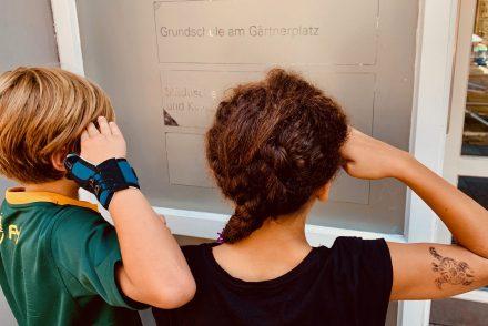 Zwei Kinder salutieren zum Abschied vor ihrer Grundschule.